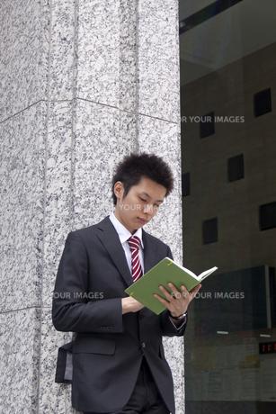 屋外 手帳を確認するビジネスマン FYI00119445
