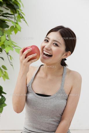 笑顔でリンゴを手にする女性 FYI00119454