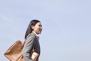 青空の下を歩く笑顔のビジネスウーマン FYI00119573