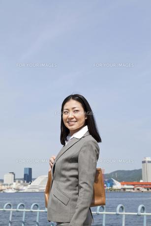 青空の下を笑顔で歩くビジネスウーマン FYI00119585