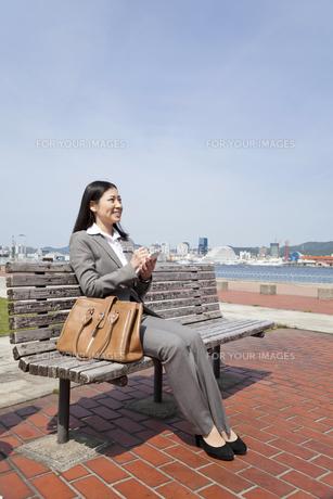ベンチに座りメモをとる若いビジネスウーマン FYI00119592