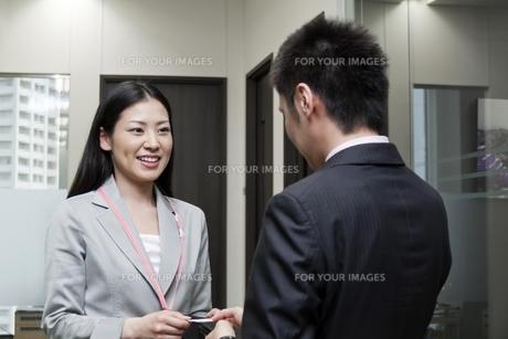 名刺を交換するビジネスマンとビジネスウーマン FYI00119600