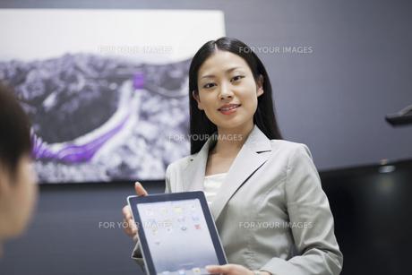 iPadで説明をするビジネスウーマン FYI00119601