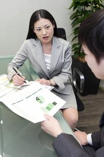 資料を手にミーティングをするビジネスマンとビジネスウーマン FYI00119605