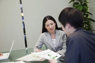資料を手に話し合うビジネスマンとビジネスウーマン FYI00119609