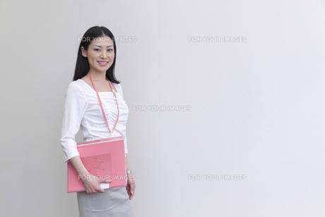 ファイルを抱えて立つビジネスウーマン FYI00119618