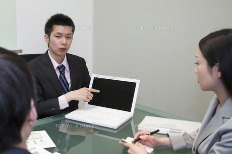 画面を指さし説明をするビジネスマン FYI00119644