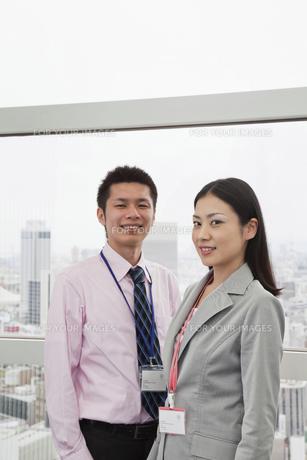 窓辺に立つビジネスマンとビジネスウーマン FYI00119651