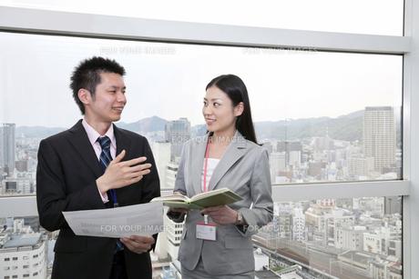 窓辺で会話をするビジネスマンとビジネスウーマン FYI00119654