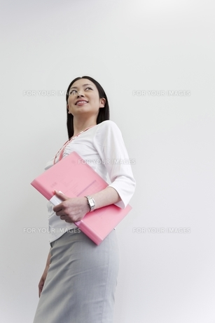 ファイルを抱え笑顔で振り向くビジネスウーマン FYI00119659