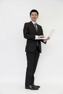 ノートパソコンを持つ若いビジネスマン FYI00119661
