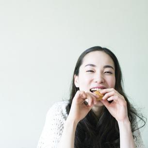 クッキーを食べる若い女性 FYI00143130
