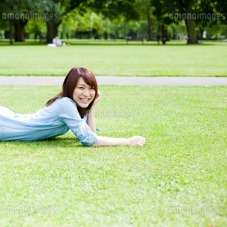 芝生に寝転んで笑顔の若い女性 FYI00143145