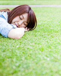 芝生に寝転んで寝ている若い女性 FYI00143148