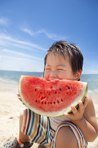 海でスイカを食べる笑顔の子供 FYI00264407