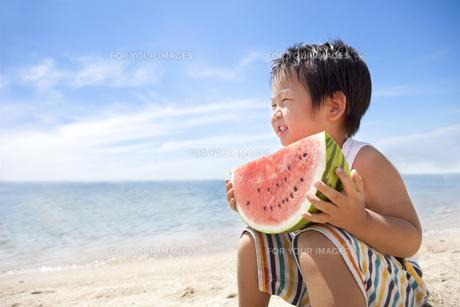 海でスイカを持って座る子供 FYI00264429