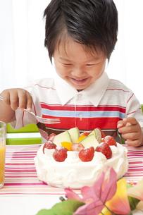 嬉しそうにバースデーケーキを食べようとする子供 FYI00264510