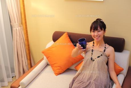 グラスをもちソファでくつろぐ笑顔の20代女性 FYI00307645