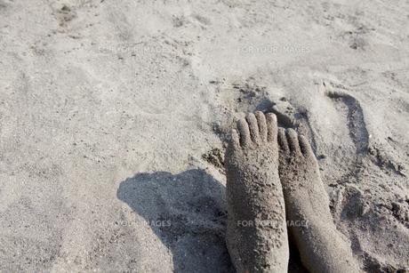 海の砂浜と砂まみれの足 FYI00318393