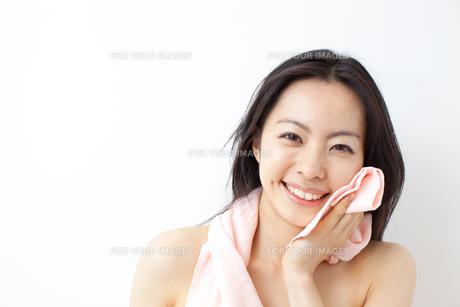 タオルで顔を拭く若い女性 FYI00401534