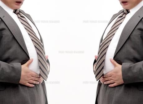 ウエストを押さえるメタボ男性二人の写真 FYI00412178