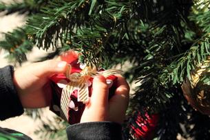クリスマスツリーと飾り付けをする子供の手 FYI00428333