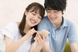 スマートフォンを見るカップル FYI00465558