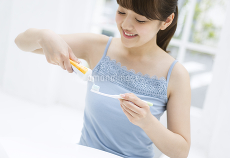 歯ブラシに歯磨き粉を付ける女性 FYI00465572