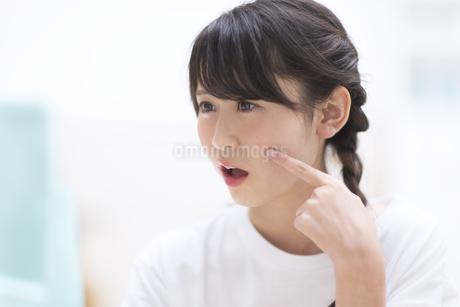 鏡で顔のチェックをする女性の素材 [FYI00465582]
