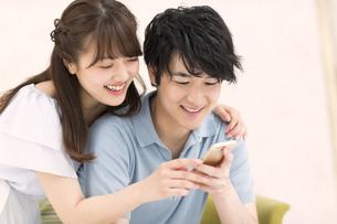 ソファーで寄り添いながらスマートフォンを見るカップル FYI00465594
