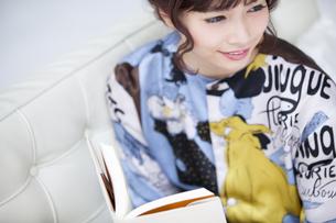 ソファーに座って本を持ち遠くを見つめる女性 FYI00465618