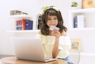 ノートPCの前でカードを手に持ち見つめる女性 FYI00465629