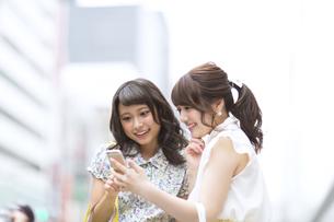 街中でスマートフォンを見る女性2人 FYI00465728