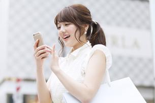 街中でスマートフォンを操作する女性 FYI00465729
