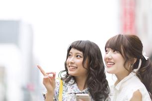 街中でスマートフォンを持ち微笑む女性2人 FYI00465730