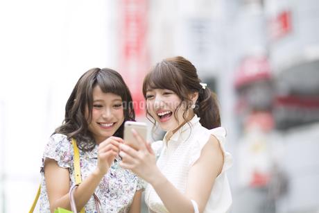 街中でスマートフォンを見る女性2人 FYI00465733