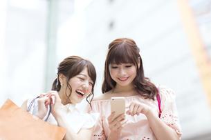 街中でスマートフォンを持ち笑う女性2人 FYI00465734