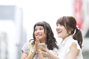 街中でスマートフォンを持ち笑う女性2人 FYI00465735