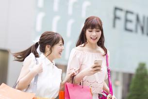 街中でスマートフォンを持ち笑う女性2人 FYI00465737