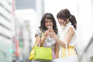 街中でスマートフォンを見る女性2人 FYI00465741