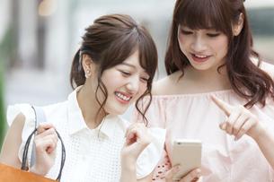 街中でスマートフォンを持ち笑う女性2人 FYI00465743