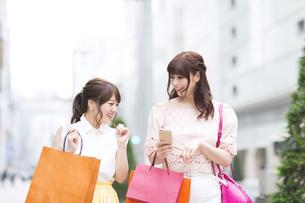 街中でスマートフォンを持ち笑う女性2人 FYI00465744