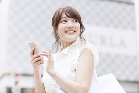 街中でスマートフォンを持ち微笑む女性 FYI00465747