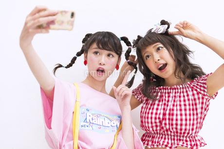 スマートフォンで写真を撮る女性2人の素材 [FYI00465758]
