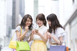 街中でスマートフォンを持ち笑う女性3人 FYI00465761