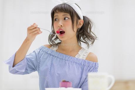 ケーキに乗っていたラズベリーを食べる女性 FYI00465780