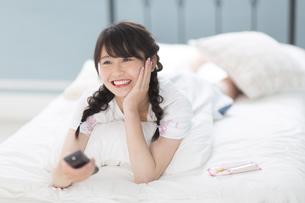 ベッドの上でリモコンを持って笑う女性 FYI00465820