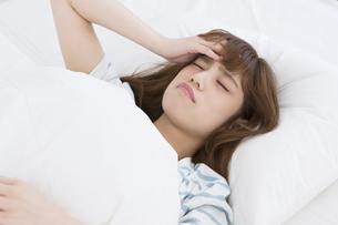 ベッドで頭痛に悩む女性 FYI00465829
