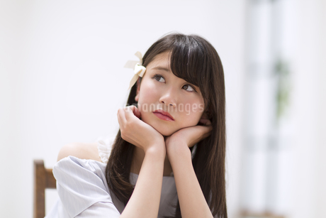 頬に両手を当て考え事をする女性 FYI00465853