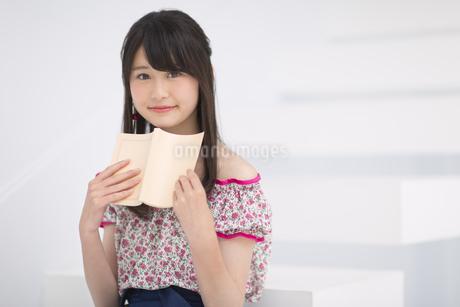 本を持ち微笑む女性 FYI00465860